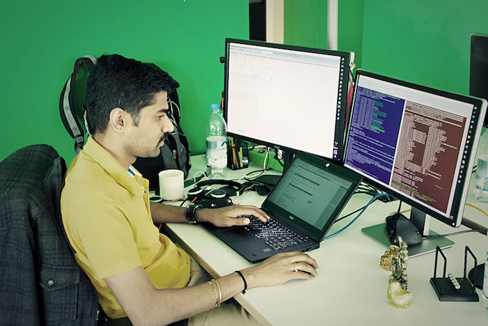 Neos IT Services, working environment, employee in front of two screens